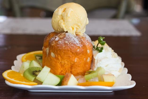 Gelato dolce con frutta a fette sul tavolo di legno, closeup mix di frutta e gelato