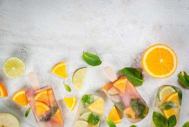 Gelato fatto in casa. bevande surgelate frutta fresca, agrumi. ghiaccioli di sangria rossa e bianca, limonata o mojito. con arance, lime, menta, mele. tavolo in pietra bianca, ingredienti. vista dall'alto