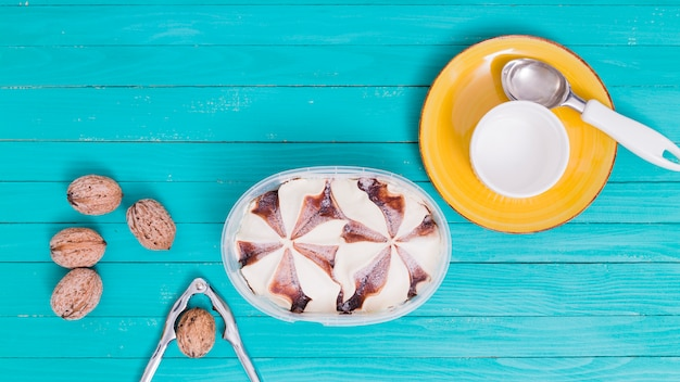 Gelato in ciotola di plastica e piatto giallo con tazza e cucchiaio e noci con nutcracke
