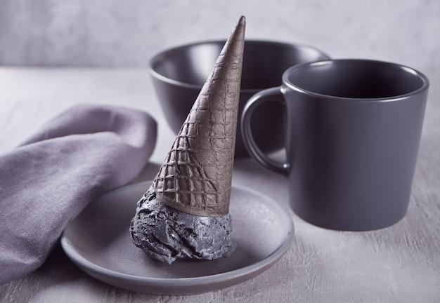 Gelato nero in coni gelato porzionati tradizionali.