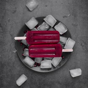 Gelato piatto laico sul bastone sul piatto con cubetti di ghiaccio