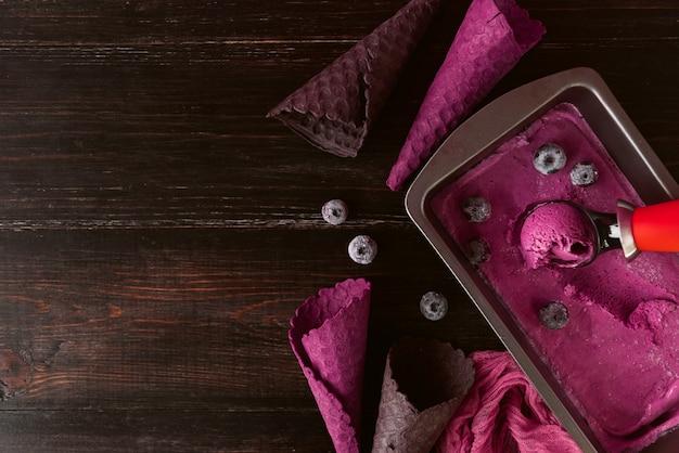 Gelato rosa con una spatola per gelato su un fondo di legno scuro con tazze di cialde