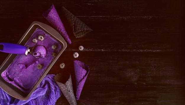 Gelato viola con una spatola per gelato su uno sfondo di legno scuro con tazze di waffle
