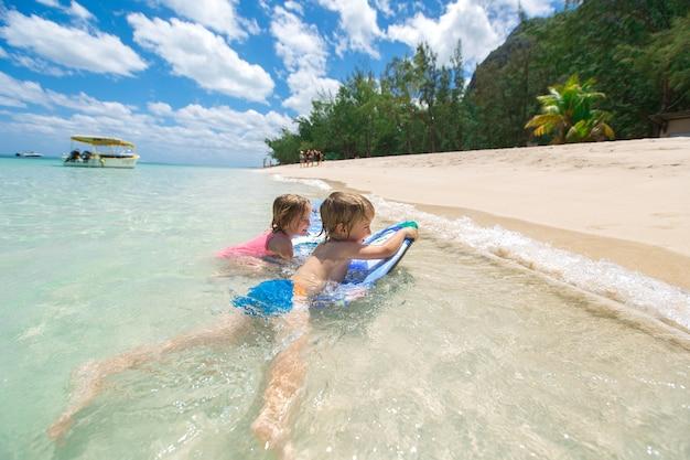 Gemella fratello e sorella per divertirsi con il surf nell'oceano