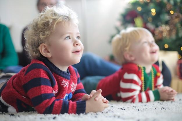 Gemelli adorabili che si siedono sul tappeto, indossando i vestiti di natale