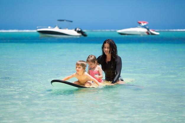 Gemelli, ragazzo e ragazza con la mamma che praticano il surfing nell'oceano su una lavagna