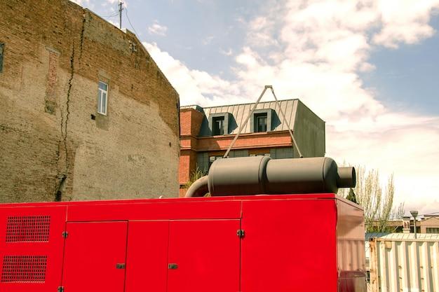 Generatore elettrico diesel stazionario con un tubo di scarico dall'alto, vicino a vecchie case.