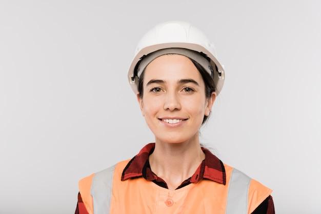 Generatore femminile sorridente abbastanza giovane in elmetto protettivo e gilet da lavoro in piedi davanti alla telecamera in isolamento