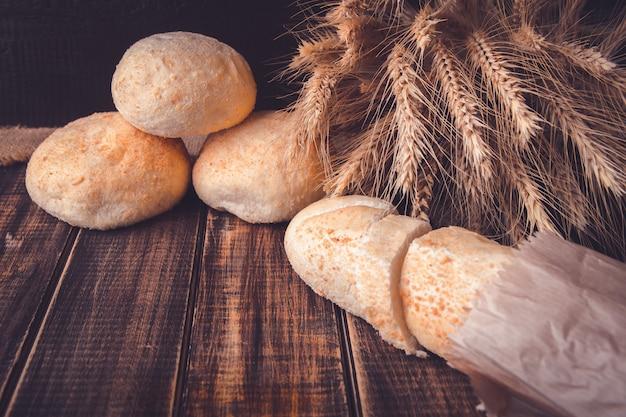 Genere differente di pane di recente cotto su una tavola di legno rustica vicino a grano. mangiare sano . avvicinamento