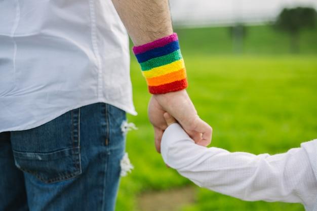 Generi con il braccialetto di bandiera dell'arcobaleno dell'orgoglio gay e suo figlio che camminano nel parco. concetto paterno