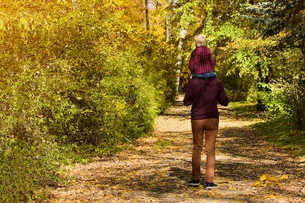 Generi con il figlio sulle sue spalle che cammina nella foresta di autunno.
