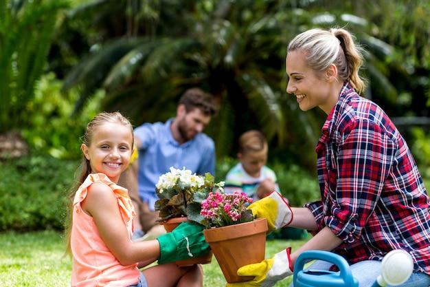 Generi dare il vaso di fiore alla figlia sorridente all'iarda