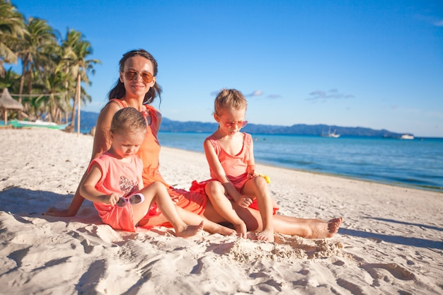 Generi e due bambini adorabili alla spiaggia il giorno soleggiato