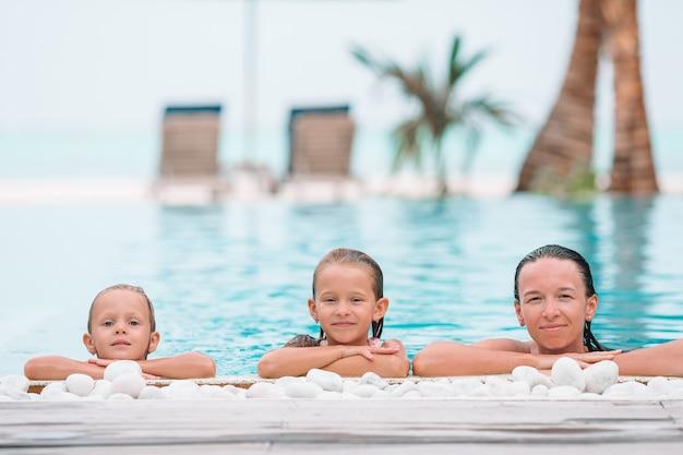 Generi e due bambini che godono delle vacanze estive nella piscina di lusso