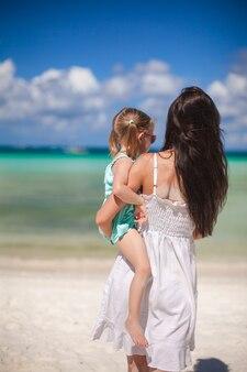 Generi e la sua piccola figlia che osserva sul mare la spiaggia tropicale