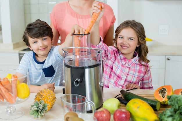 Generi ed i suoi due bambini che producono il succo di frutta fresca in cucina