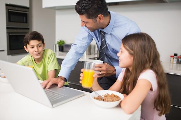 Generi facendo uso del computer portatile e dei bambini che mangiano prima colazione in cucina