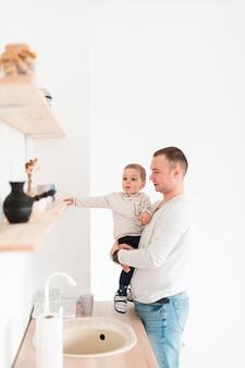 Generi il bambino della tenuta mentre nella cucina con lo spazio della copia