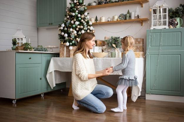 Generi il gioco con il suo bambino nella cucina di natale a casa.