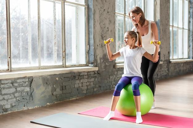 Generi la figlia d'aiuto che si siede sulla palla di esercizio che tiene i pesi