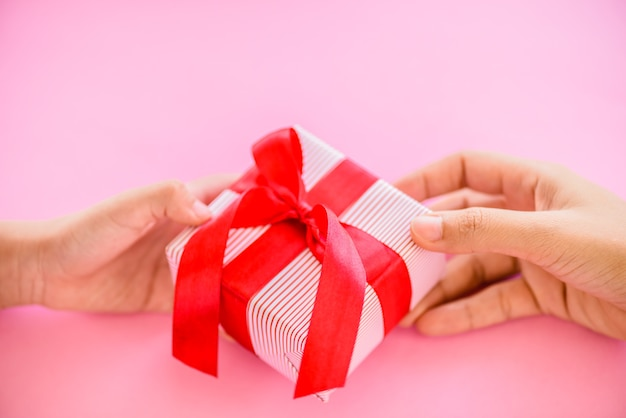 Generi la mano che dà un contenitore di regalo con il nastro rosso al suo bambino.