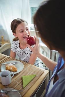 Generi la mela d'alimentazione a sua figlia mentre mangiano la prima colazione