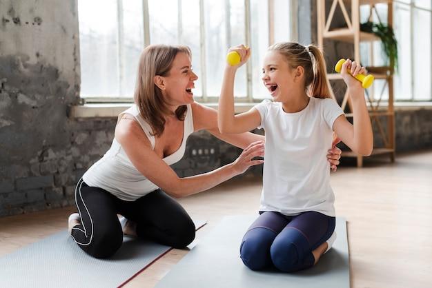 Generi solleticare la figlia che tiene i pesi sulla stuoia di yoga