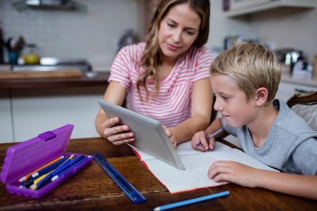 Generi usando una compressa digitale mentre aiutano il figlio con i suoi compiti