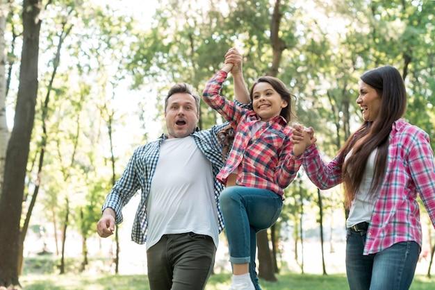 Genitore che alza la figlia al parco