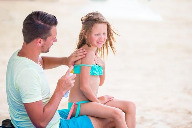 Genitore che applica la crema solare al naso del bambino.