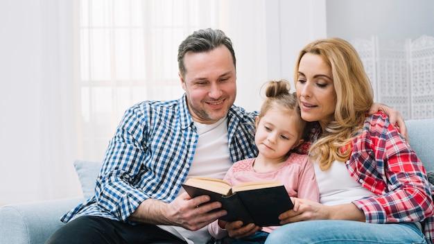 Genitore che si siede con la figlia che si siede sul libro di lettura del sofà