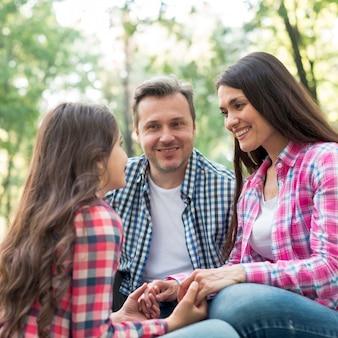 Genitore sorridente che esamina la loro figlia durante la seduta nel parco