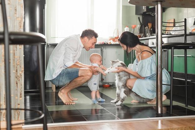 Genitore sorridente che gioca con il gatto e il loro bambino in cucina