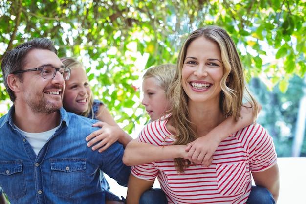 Genitori allegri che danno sulle spalle ai bambini