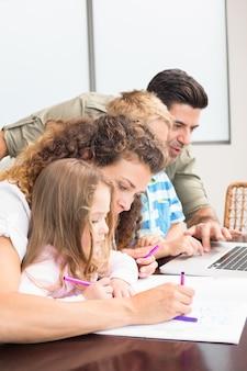 Genitori attraenti che colorano e usano il laptop con i loro bambini