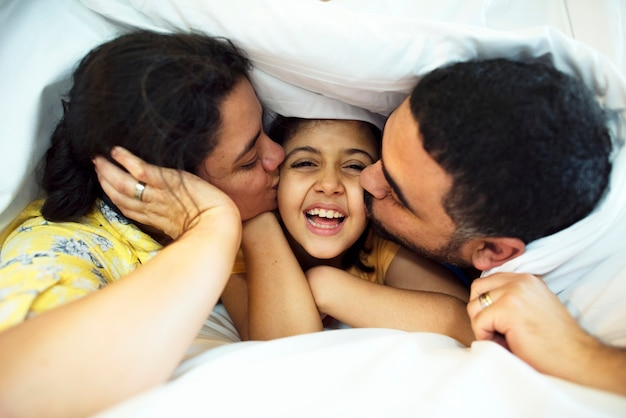 Genitori che danno baci alla figlia sulle guance