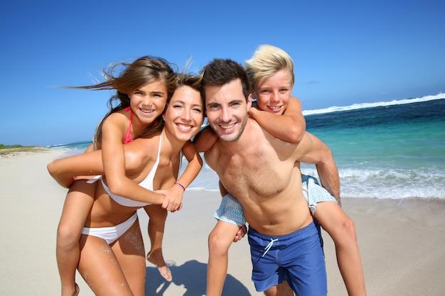 Genitori che danno cavalluccio ai bambini in spiaggia
