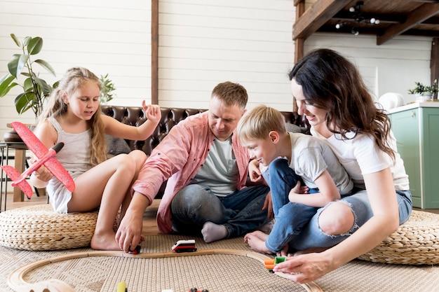 Genitori che giocano con i bambini in salotto