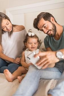 Genitori che mostrano smartphone alla figlia che ride