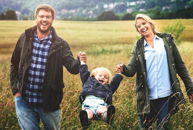 Genitori della famiglia che si tengono per mano ragazzo che oscilla concetto