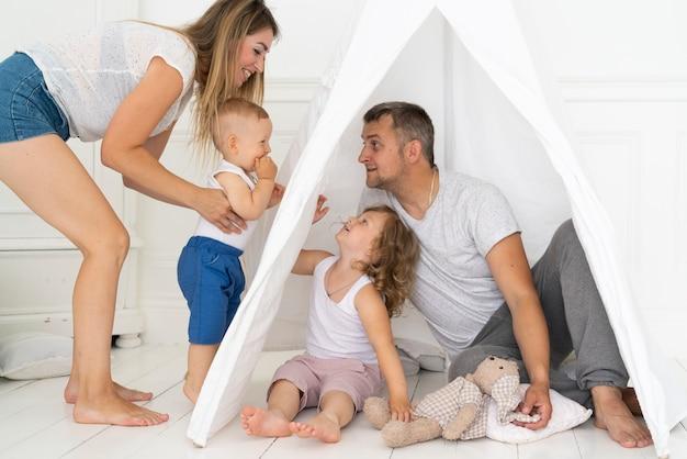 Genitori della foto a figura intera che giocano con i bambini con la tenda