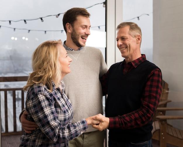 Genitori di smiley che abbracciano figlio a casa