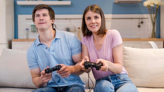 Genitori di vista frontale che giocano ai videogiochi a casa