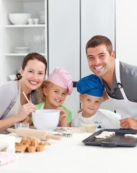 Genitori e bambini che giocano insieme in cucina