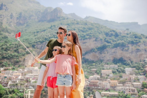 Genitori e bambini che prendono selfie foto sulla città di positano in italia sulla costiera amalfitana