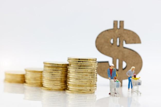 Genitori e bambini con la carta di acquisto che sta prima della pila e del simbolo di dollaro delle monete.