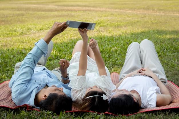 Genitori e bambini stanno giocando il tablet sul tappeto nel parco.