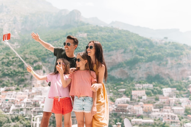 Genitori e figli che prendono selfie foto di sfondo positano città in italia sulla costiera amalfitana