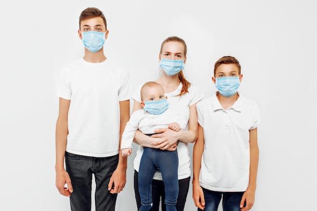 Genitori e figli della famiglia indossano maschere mediche per prevenire infezioni, malattie respiratorie trasportate dall'aria, coronavirus