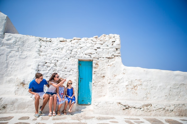 Genitori e figli in strada del tipico villaggio tradizionale greco con pareti bianche
